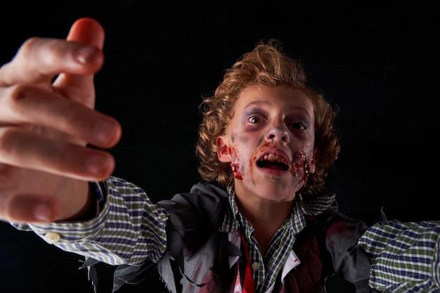 Фото мальчика, замаскированного под зомби с кровью и блеском с выражением страха. хэллоуин
