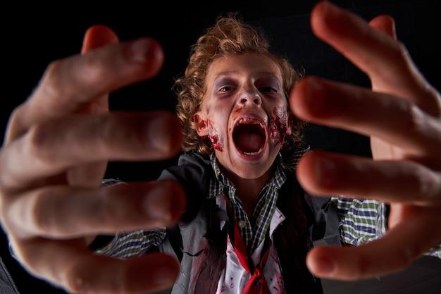 Фото мальчика, замаскированного под зомби с кровью и блеском, с руками впереди и выражением страха. хэллоуин