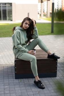 通りでコーヒーを飲みながらベンチに座っているオリーブのパーカーとジョガーの魅力的な若い女の子のストックフォト。