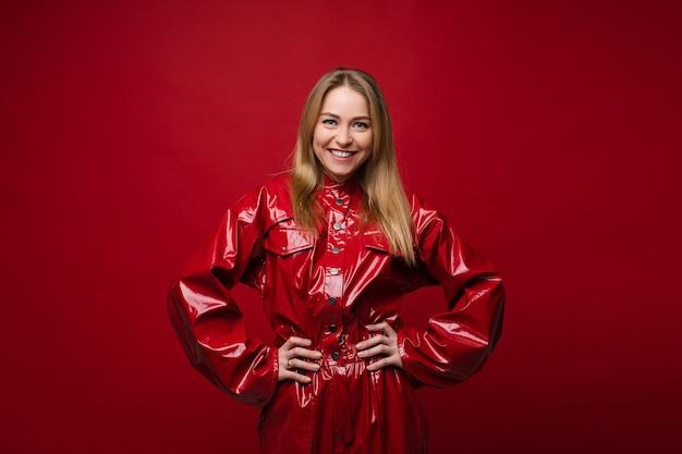 Фото запаса веселой красивой кавказской блондинки в стильной красной кожаной куртке с руками на талии, улыбаясь в камеру. изолировать на ярко-красном фоне.