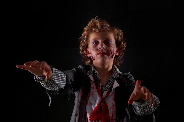 Фото ребенка, замаскированного под зомби с кровью и блеском, с поднятыми руками при ходьбе. хэллоуин
