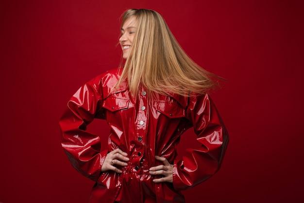 Фото танцующей веселой женщины с длинными светлыми волосами в движении. на ней стильный красный кожаный комбинезон.