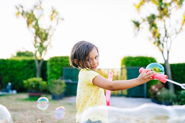 晴れた日の日没時にシャボン玉で通りで遊んでいる女の子のストックフォト
