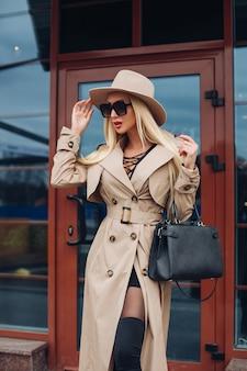 Сток-фото великолепной уверенной в себе блондинки в модном бежевом плаще, бежевой шляпе и черных солнцезащитных очках с кожаной сумочкой, стоящей в городе.