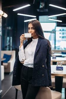 椅子のそばに立って、モダンなレストランで白いカップから熱い淹れたてのコーヒーを一口飲んでいる茶色の髪のジャケット、ブラウス、ズボンのゴージャスなエレガントな実業家のストックフォト