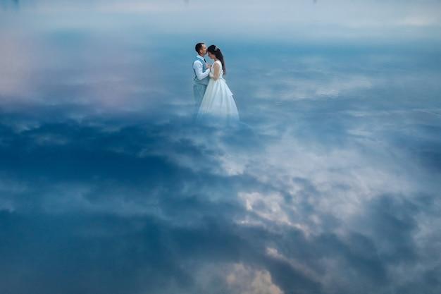 スーツとウェディングドレスで手をつないで顔を合わせて立っているちょうど夫婦のストックフォト。空の雲に囲まれて立っているような模倣。