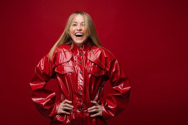 Сток фото смеющейся красивой девушки в модной красной кожаной куртке. она изолирована на красном фоне. смеющаяся девушка со светлыми волосами, взявшись за руки на талии.