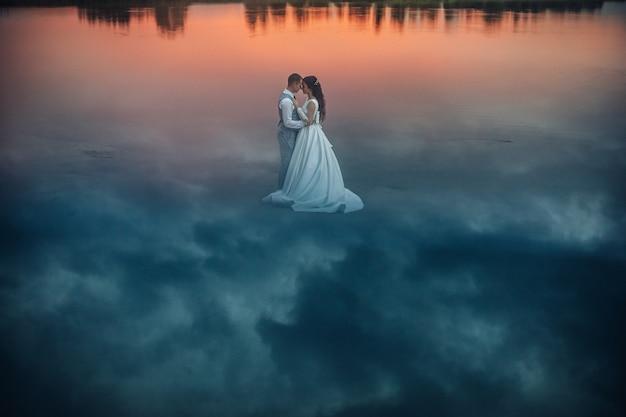 ウェディングドレスを着たロマンチックな花嫁とその上に空の反射で濡れた砂の上に立って向かい合って抱き締めるスーツの新郎のストックフォト。地面に反射する雲が幻想的な景色を作ります。