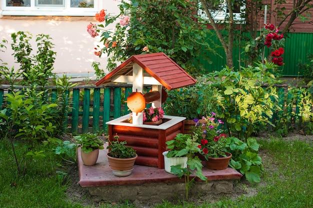 Фото небольшого сада на заднем дворе. подделайте колодец с цветами в горшках.