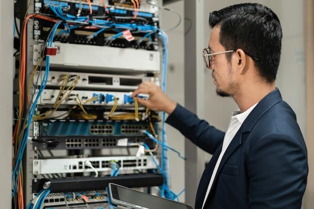 ネットワークサーバールームのサーバーキャビネットでネットワークケーブルを接続するために働いているタブレットを持っている若いネットワーク技術者のストックフォト。ネットワークサーバールームで働くitエンジニア