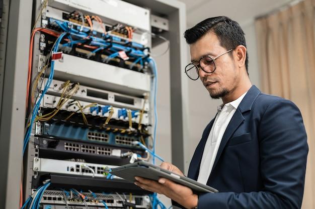 Фондовый фото молодой сетевой техник, держащий планшет, работающий для подключения сетевых кабелей в серверном шкафу в сетевой серверной комнате. ит-инженер, работающий в сетевой серверной комнате