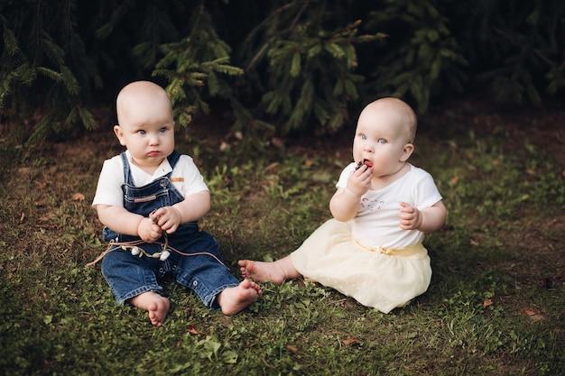 숲에서 잔디에 앉아 사랑스러운 작은 아기의 재고 사진. 작은 형제와 자매는 숲의 푸른 잔디에 앉아 열매를 먹고 있습니다.