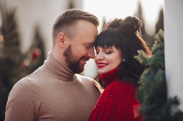 モミの木に囲まれた愛情のこもったカップルのストックフォト。彼の魅力的な妻を見ている男。