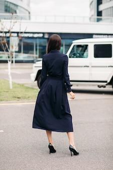 通りに立っている長いスカートと黒い革のかかとと黒い綿のドレスを着た認識できないブルネットの女性のストックフォト。