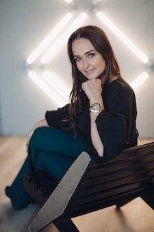 黒のブラウスと濃い緑色のズボンで魅力的なブルネットの若い大人の女性のストックフォトは、多くのランプで白い壁にポーズをとっています。