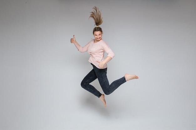 陽気な屈託のないブロンドの女性が白い背景に親指を立てて空中でジャンプのストックフォト。親指を立ててカメラに笑みを浮かべてジャンプする女性。