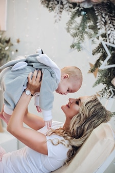 ブランコでリラックスしたウサギの衣装で赤ちゃんの息子と遊ぶ陽気な母親のストックフォト。クリスマス。