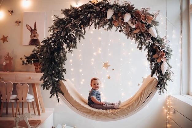 전나무 나뭇가지와 솔방울로 장식된 아늑한 그네에 앉아 있는 귀여운 소년의 사진. 화환으로 장식된 벽에 집에서 아름다운 그네에 앉아 있는 아이.
