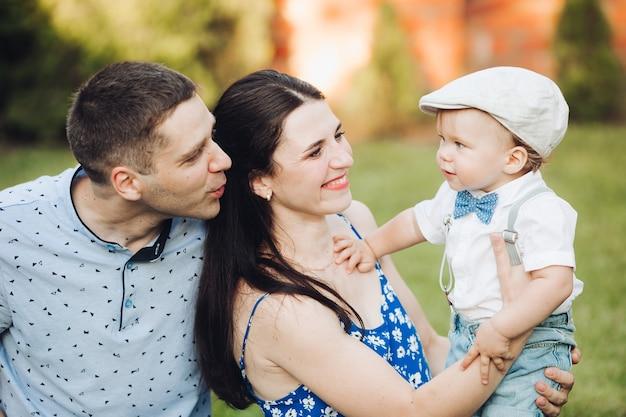 公園で息子とお父さんとお母さんのストックフォト。美しい笑顔の母親が息子を腕に抱き、父親が母親の後ろで彼に微笑んでいます。帽子と弓をかぶった少年。幸せな家族の概念。