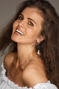 裸の肩でカメラを見ているウェーブのかかった髪のゴージャスな笑顔のブルネットのストックフォト。美しい幸せな女性のクローズアップ。