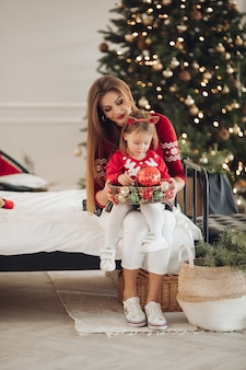 Фото запаса любящей матери в зеленом платье, дающей ее маленькой дочери в пижамном платье рождественский подарок. они рядом с красиво украшенной елкой под снегопадом.