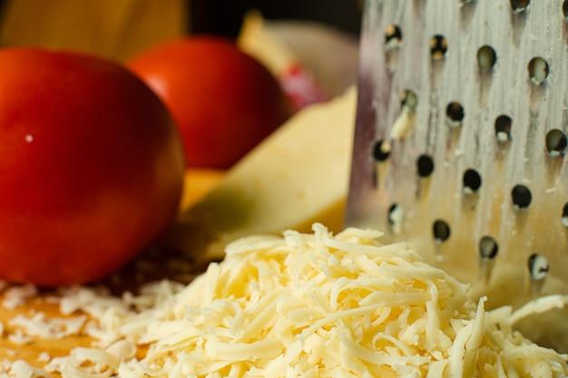 クローズアップでぼやけた背景に赤いトマトのカップルとシュレッドチーズとおろし金の山のストックフォト。