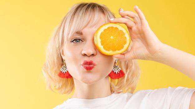 오렌지가 반으로 갈라진 흰색 티셔츠를 입은 긍정적인 금발의 젊은 여성이 눈 앞에서 그것을 들고 카메라를 향해 입술을 내밀고 있는 사진. 노란색 배경에 격리합니다. 여름 개념입니다.