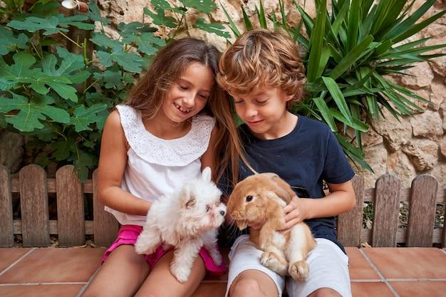 두 아이가 옆으로 앉아 있는 사진, 한 명은 무릎에 개가 있고 다른 한 명은 토끼와 함께 있습니다. 애완 동물과 가족