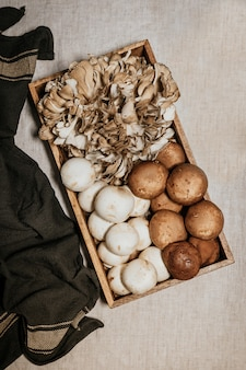 Stock photo of overhead view on box full of mushrooms, shiitake, hen of the woods, on gray table and tablecloth.