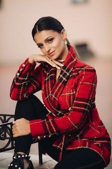 Foto di stock ritratto di giovane ragazza attraente in luminoso trench a quadri, pantaloni neri e stivali alla moda seduto su una panchina nel parco. guardando la fotocamera con aria sognante.