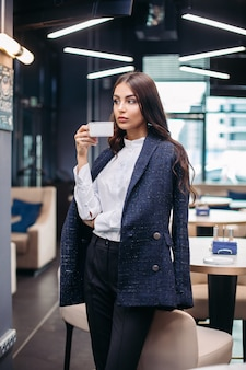 Stock photo portrait of a confident gorgeous businesswoman in jacket over shoulders, white formal blouse and black trousers with coffee in restaurant