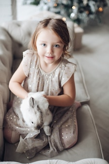 Stock photo portrait of cute little girl in festive dress with lovely bunny in her arms sitting on couch. unfocused decorated christmas tree in background.