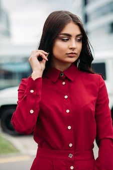 Stock photo portrait of a fashion model with long brown hair and make up wearing bright red dress with buttons up and collar. holding hand at her hair, looking away emotionlessly.