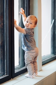 Stock photo portrait in full length of cute little baby boy standing by the window. he is looking back at camera. holding his hand up on the window.