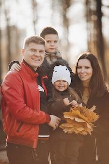 스톡 사진 아들과 딸이 노란 잎을 잔뜩 들고 카메라를 보며 웃고 있는 아름다운 명랑 가족의 초상화. 화창한 단풍 공원에서 함께 졸리 백인 가족입니다.