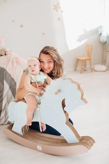 스톡 사진 회색 티셔츠와 청바지를 입은 아름다운 미소 짓는 어머니의 초상화는 사랑스러운 작은 딸을 손에 들고 행복하게 카메라를 바라보고 있습니다....