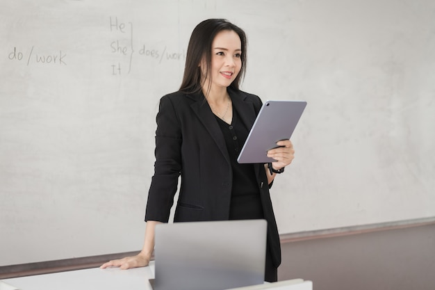 Фото портрет уверенной жизнерадостной азиатской женщины-учителя в черной униформе делового костюма с цифровым планшетом и ноутбуком, чтобы преподавать современный язык в классе