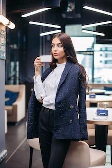스톡 포토 어깨 너머 재킷에 자신감이 화려한 사업가의 초상화, 흰색 정장 블라우스와 레스토랑에서 커피와 검은 바지