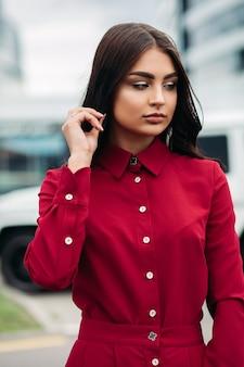 長い茶色の髪とボタンアップと襟付きの真っ赤なドレスを着てメイクアップのファッションモデルのストックフォトの肖像画。彼女の髪に手をかざし、無表情に目をそらしている。