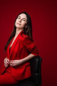 椅子に座ってカメラを見ている赤いジャケットの黒髪のゴージャスな自信の実業家のストックフォトの肖像画。真っ赤な背景に分離します。スペースをコピーします。
