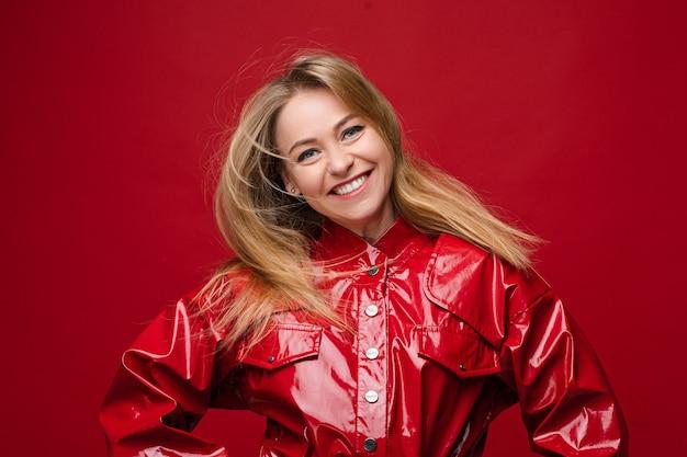Фондовый фото портрет прекрасной веселой женщины со светлыми волосами и макияж в красной кожаной куртке, движущейся на красном фоне.