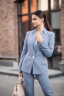 Фондовый фото портрет привлекательной элегантной брюнетки с хвостом в серовато-синем костюме с бежевой сумкой, стоящей на улице.