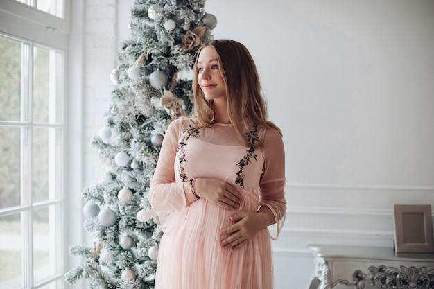 彼女の妊娠中の腹に手をつないで、しんみりと目をそらしているピンクのドレスを着た魅力的な官能的な白人女性のストックフォトの肖像画。自宅でクリスマスツリーに対して美しい妊婦。