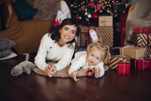 ラップされたクリスマスプレゼントと枕の上に木の床に横たわっている小さな金髪の娘と魅力的な若い大人の母親のストックフォトの肖像画。女の子は赤いクリスマスボールで遊んでいます。