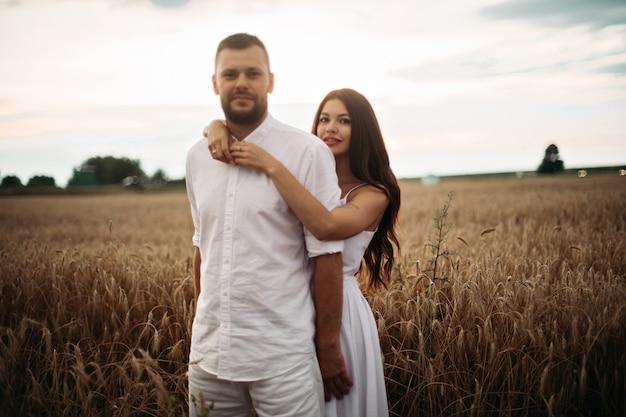 麦畑で抱き締める白い服で彼のゴージャスなガールフレンドを抱き締めるひげを生やしたボーイフレンドのストックフォトの肖像画。背景の美しい麦畑。