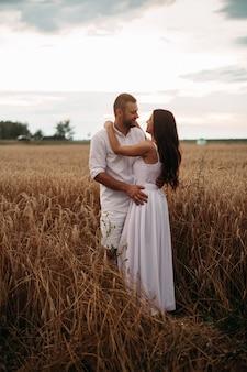 Фото портрет бородатого парня, обнимающего свою великолепную подругу в белой одежде, обнимая в пшеничном поле. красивое пшеничное поле на заднем плане.