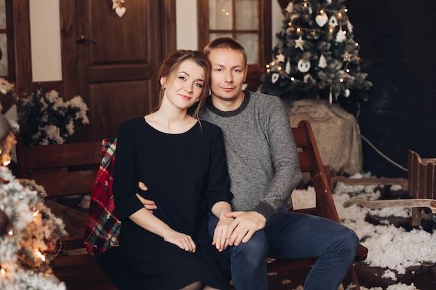 Фондовый фото портрет красивой молодой взрослой пары, сидящей, прижимаясь к деревянной скамейке в рождественском интерьере