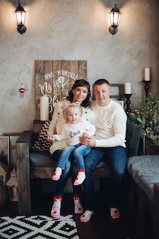 居心地の良い部屋で降雪の下で小さなソファに座って寄り添う膝の上に小さな娘と陽気な白人家族のストックフォトの肖像画。彼らは娘を抱きしめてカメラを見ています。