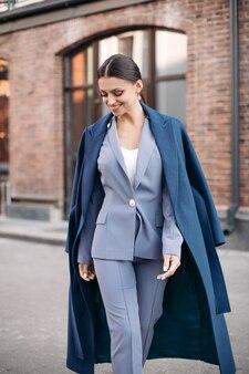 Фондовый фото портрет великолепной брюнетки-бизнесвумен в стильном серо-синем костюме, синем пальто на плечах и бежевой кожаной сумке на руке. улыбается в камеру.