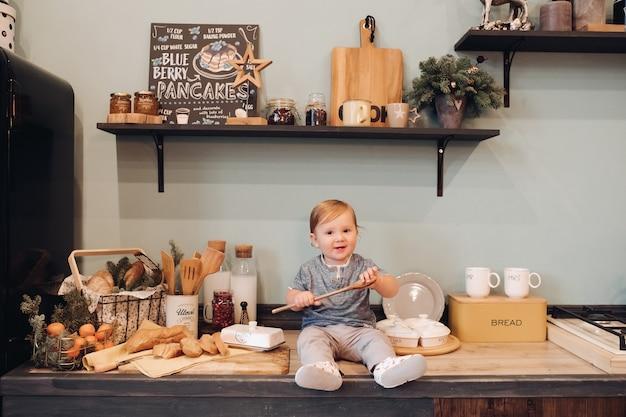 Фондовый фото портрет прекрасного мальчика, сидящего на кухонном прилавке и играющего с деревянной ложкой. рождественские украшения. еловые ветки на кухне.